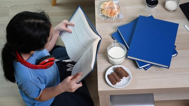 Sopra la vista del libro di lettura della giovane ragazza asiatica mentre era seduto sul pavimento nel soggiorno