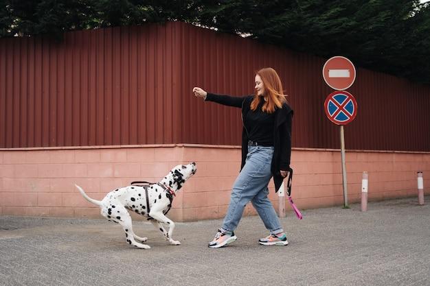 Vista della giovane femmina caucasica che gioca e addestra il suo cane dalmata