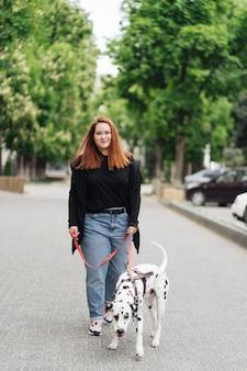 Vista di una giovane donna caucasica che cammina in città durante la mattinata con un cane dalmata