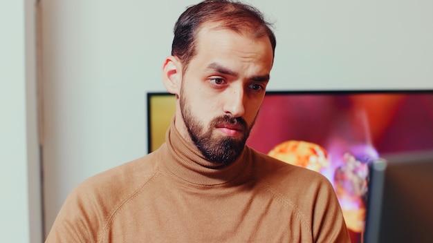 Vista del giovane sviluppatore di giochi che lavora al computer in ufficio a casa durante la notte.