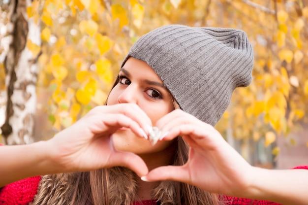 La vista della giovane donna con il cappello di lana grigio che fa un cuore modella con le sue dita nel parco