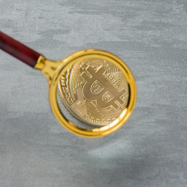 Visualizzazione e aumento di bitcoin attraverso una lente di ingrandimento. moneta elettronica