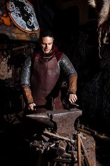 Viking forgia armi e spade nella fucina. un uomo travestito da guerriero è nella fucina.