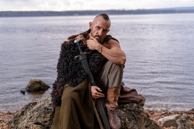 Viking è pensieroso e siede su una pietra tenendo una spada inserita in un fodero