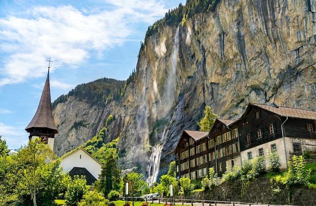 La chiesa del villaggio e le cascate di staubbach a lauterbrunnen - canton berna, svizzera