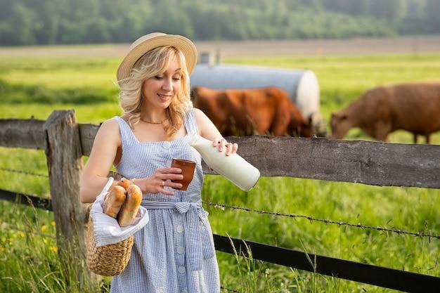 Ragazza del villaggio che versa il latte in un bicchiere, sullo sfondo di campi con mucche al pascolo