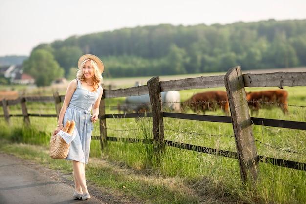 Ragazza del villaggio con un sacco di latte e pane che attraversa i campi con le mucche al pascolo