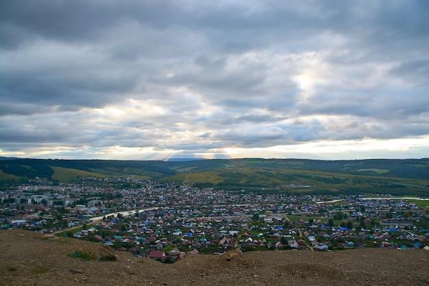 Villaggio di montagna con vista a volo d'uccello del sole e delle nuvole.
