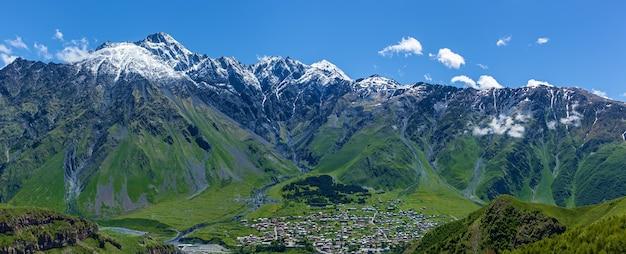 Villaggio sulle cime innevate delle montagne sfondo nel distretto di kazbegi militarygeorgian road