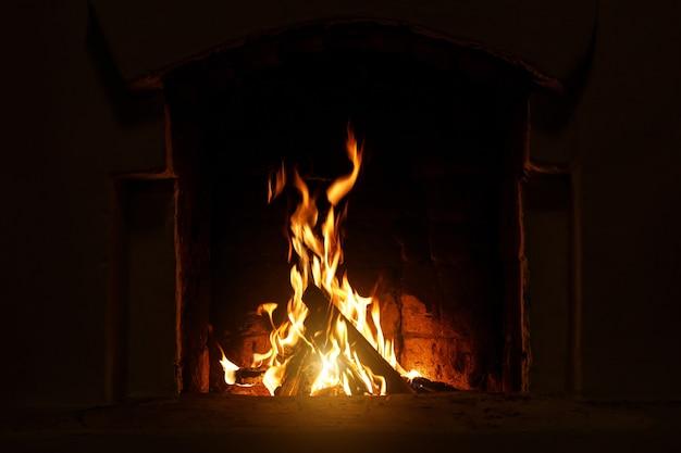 Stufa del villaggio a legna e fuoco. legna che brucia all'interno del forno tradizionale.