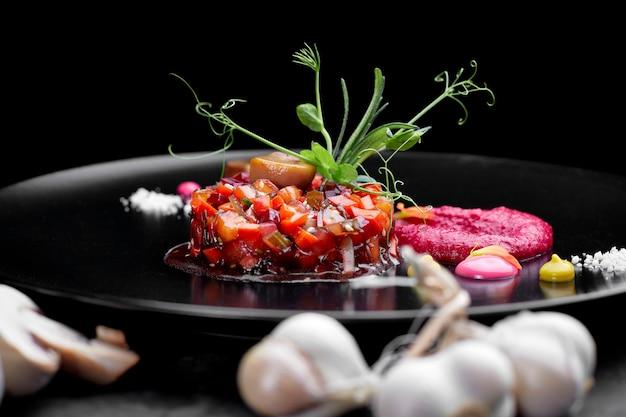Insalata di vinaigrette su sfondo nero, su un piatto nero con aglio