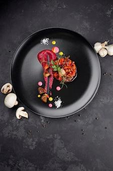Insalata di vinaigrette su sfondo nero, con funghi e aglio