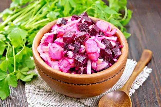 Insalata di vinaigrette con sottaceti o crauti, patate, barbabietola e cipolla, condita con olio vegetale in una ciotola su tela, prezzemolo, cucchiaio su uno sfondo di tavola di legno