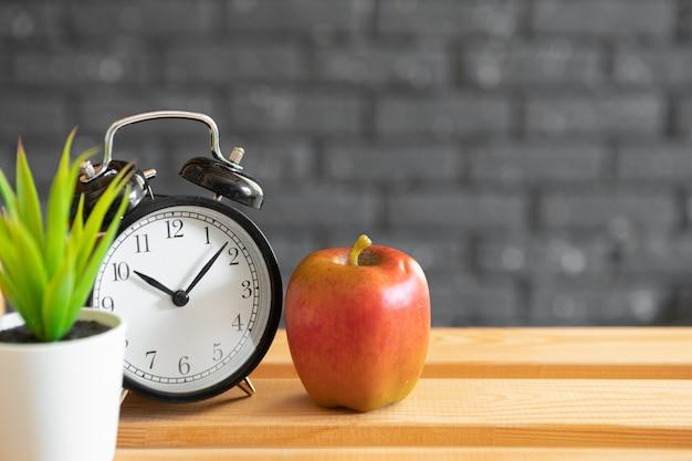 Sveglia e mela d'annata sullo scrittorio di legno