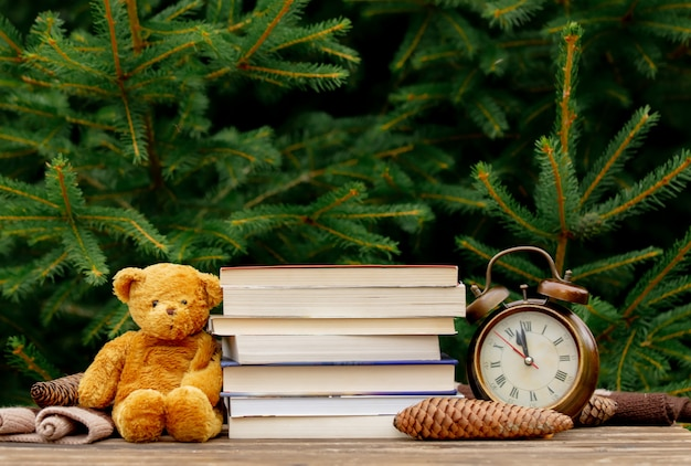 Sveglia, orsacchiotto e libri d'annata sulla tavola di legno con i rami attillati su fondo