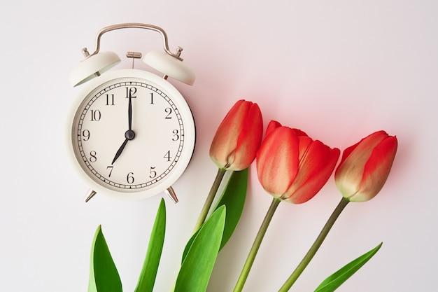 Sveglia vintage e tulipani fiori in vaso su sfondo bianco. tempo di primavera. risparmio di tempo. concetto di mattina