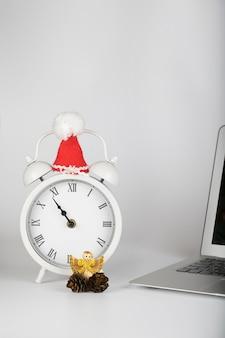 Sveglia vintage con cappello di babbo natale posizionato vicino al laptop. sfondo grigio