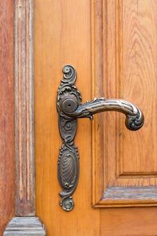 Maniglia della porta d'epoca d'epoca sulla vecchia porta di legno, vecchia manopola della porta