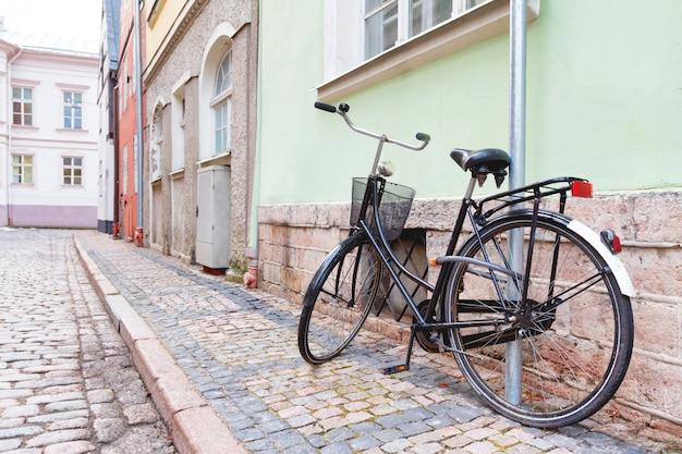 Parcheggio della bicicletta d'annata contro il muro alla via della città