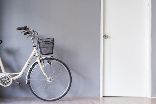 Parcheggio per biciclette d'epoca vicino al muro grigio e porta bianca