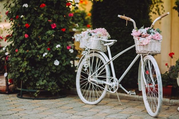 Bicicletta vintage con cesto con fiori rosa.