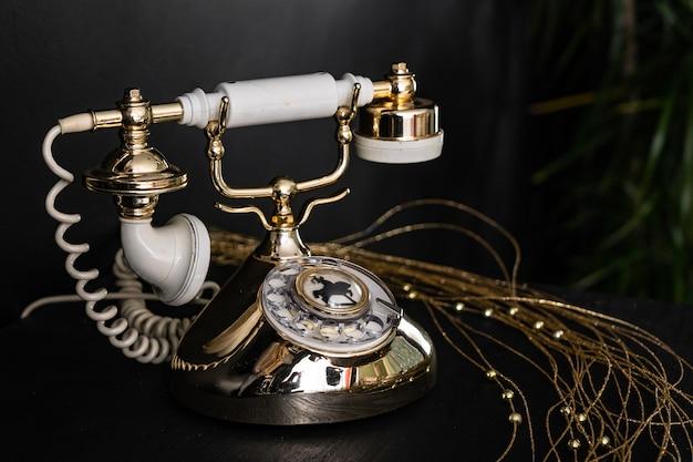 Telefono vintage nero su un vecchio sfondo di tavolo in legno