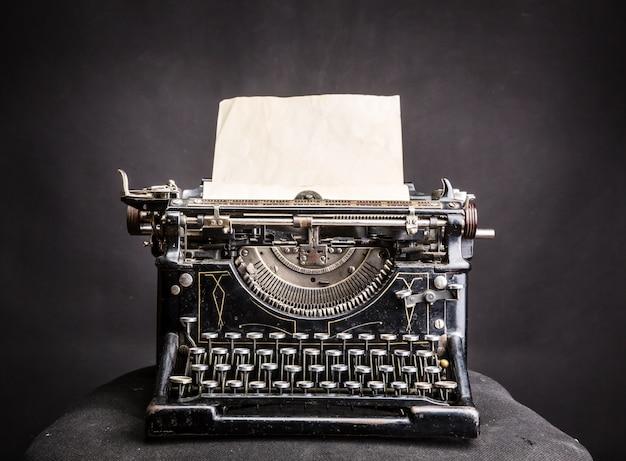 Macchina da scrivere nera vintage con foglio di carta inserito