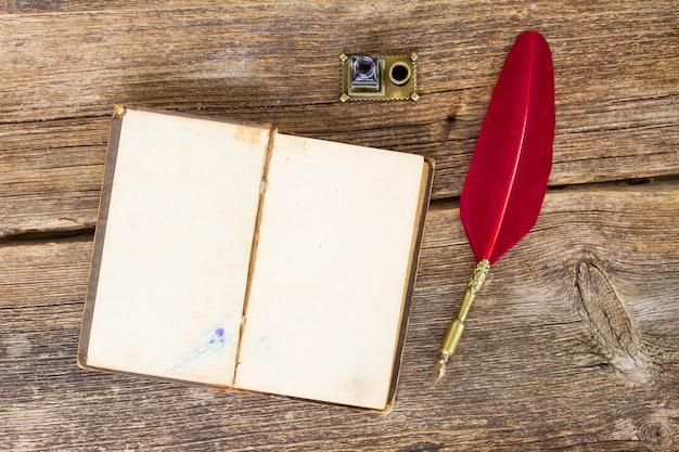 Libro aperto in bianco dell'annata con piuma rossa, vista dall'alto