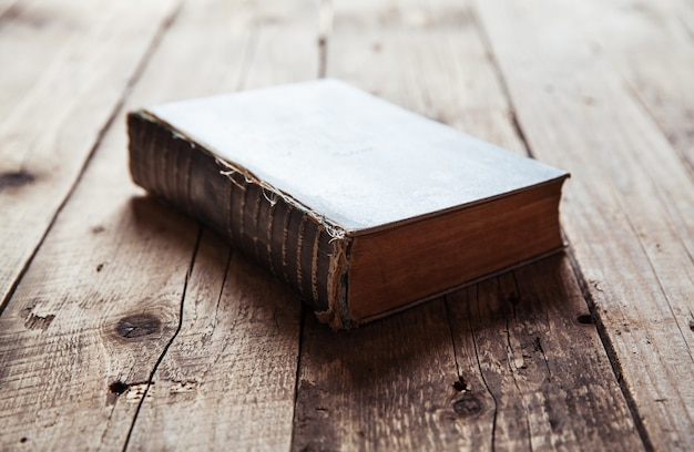 Libro d'epoca, aperto, sul vecchio tavolo in legno.
