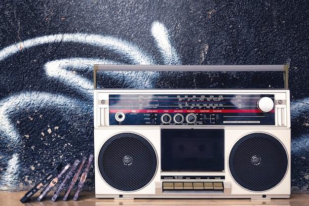 Boombox vintage con cassette sul pavimento su un graffito