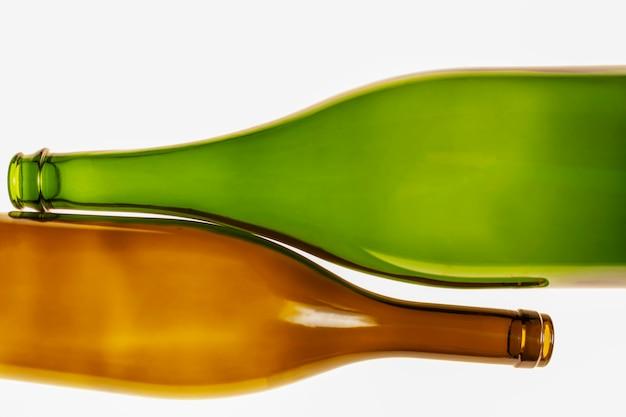 Bottiglie d'annata dei colori verdi e marroni su un bianco
