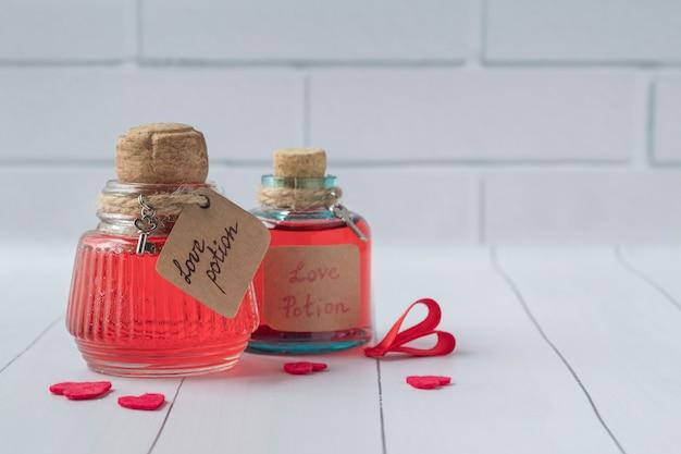 Bottiglie d'annata con pozioni d'amore magiche sulla tavola di legno bianca, spazio per testo