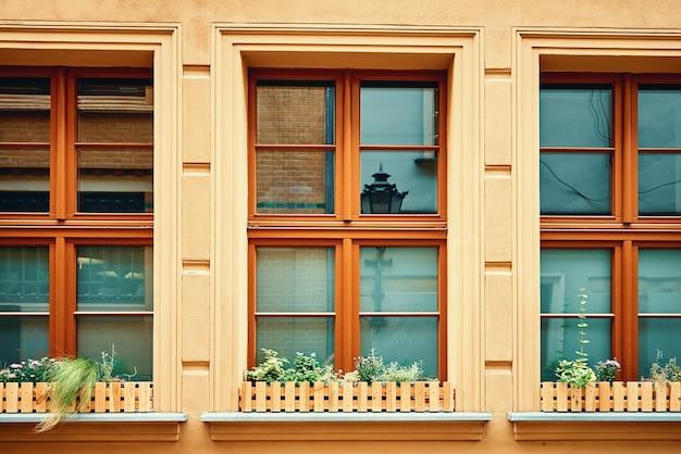 Facciata di edificio vintage con finestre e fiori sul davanzale