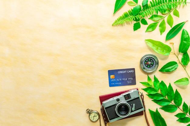 Macchina fotografica d'epoca, carta di credito, passaporto, orologio da tasca e bussola sul tavolo