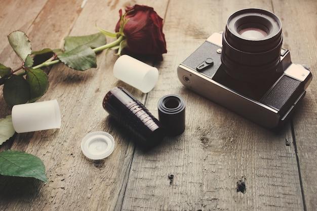 Macchina fotografica d'epoca e rosa sul tavolo di legno