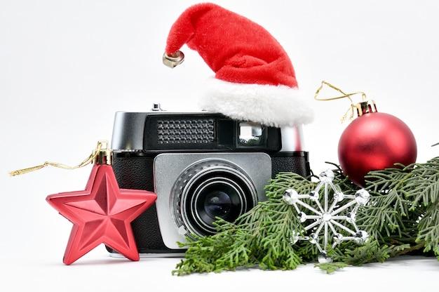 Fotocamera vintage circondata da albero di natale e giocattoli su sfondo bianco isolato