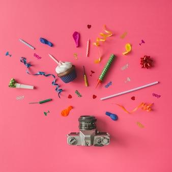 Fotocamera vintage con articoli per feste colorate sulla parete rosa. lay piatto.