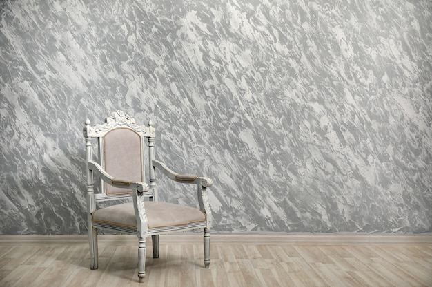 Sedia vintage contro un muro grigio strutturato.