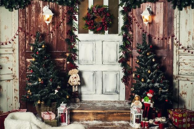 Decorazione natalizia vintage della porta d'ingresso con doni e luci