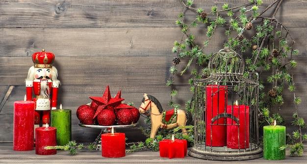 Decorazioni natalizie vintage con candele rosse, giocattoli antichi schiaccianoci e cavallo a dondolo. immagine dai toni in stile retrò