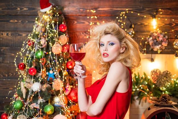 Ragazza di natale vintage con acconciatura retrò e trucco pinup sopra l'albero di natale. concetto della gente di feste e bevande della festa di natale. vestiti alla moda del nuovo anno.