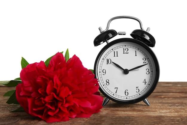 Orologio vintage e bouquet di peonie su tavola di legno