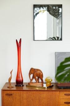 Composizione vintage su mobile in legno con vaso rosso retrò, registratore in vinile, specchio ed eleganti accessori personali.