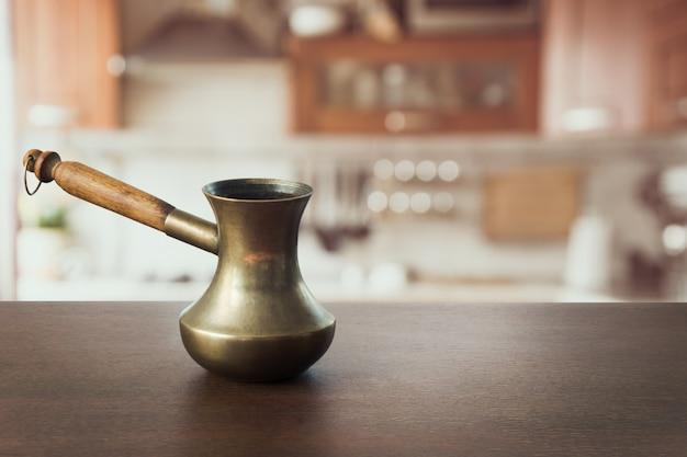 Cezve di rame d'annata sul ripiano del tavolo di legno e cucina moderna come fondo per i prodotti dell'esposizione.