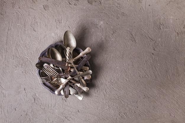 Posate e utensili vintage su sfondo di cemento. collezione vintage, vista dall'alto