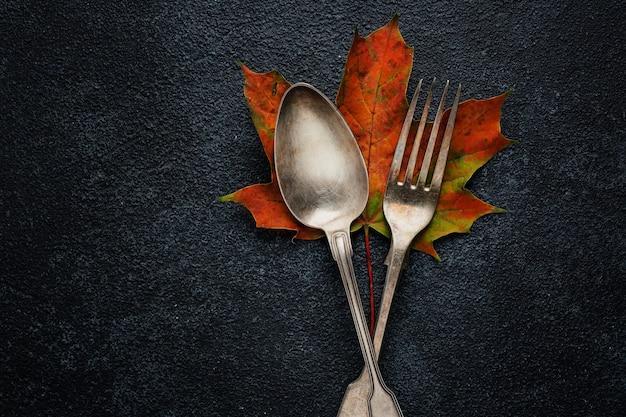 Posate vintage con foglie di autunno sulla superficie scura