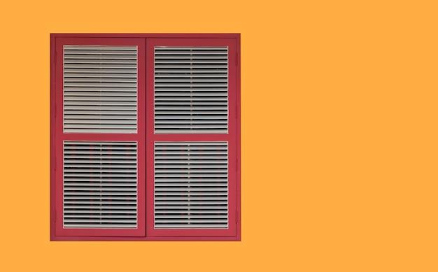 Persiane vintage rosso scuro e finestre in legno isolate su giallo con spazio copia e percorso di ritaglio