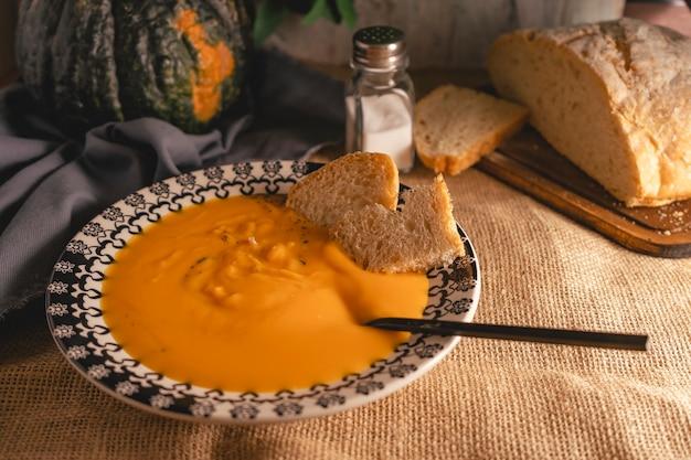 Piatto fondo vintage con crema di zucca e carote in un ambiente country o rustico con una tela da imballaggio