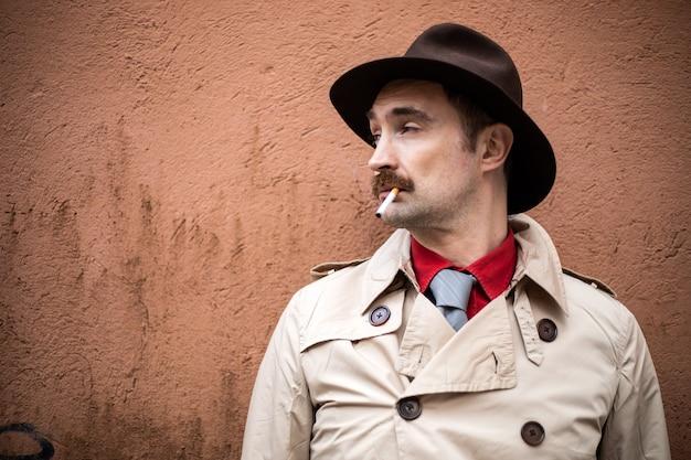Detective vintage che fuma una sigaretta in una baraccopoli di città