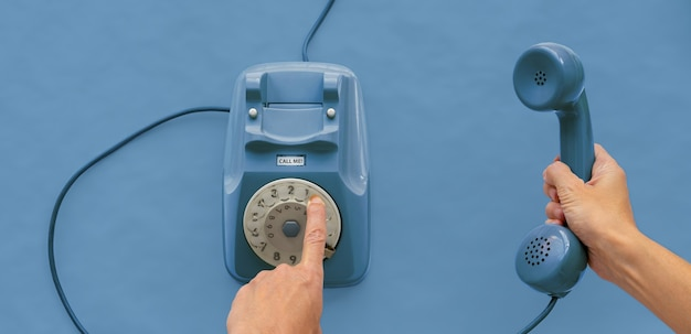 Una cornetta telefonica vintage con una mano e sfondo blu